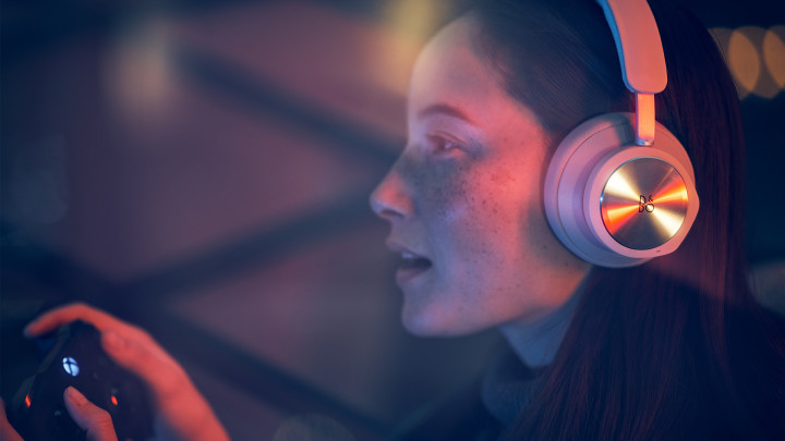 Woman playing XBOX with Beoplay Portal sand