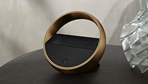 Beoremote Halo remote placed on wooden cabinet
