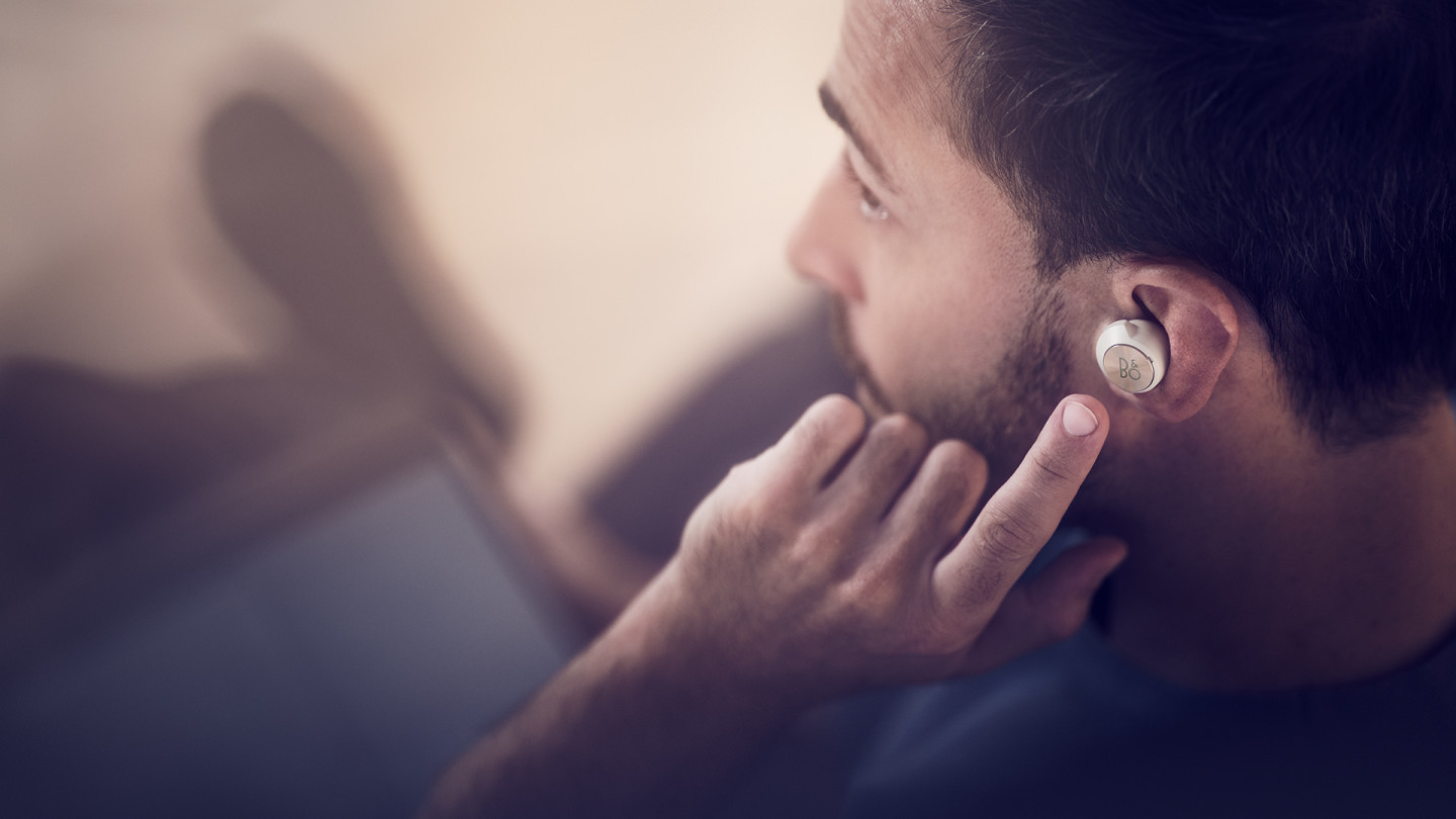A man using the touch control on his left Beoplay EQ earbud