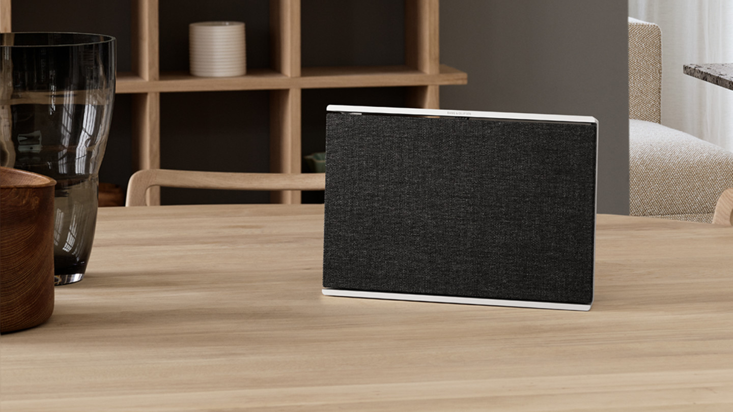 Beosound Level Natural - Dark Grey placed upright on a wooden table in a living room