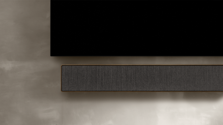 Beosound Stage in smoked oak hanged on a wall below a tv screen