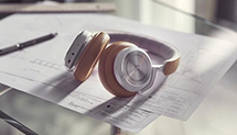 Beoplay HX headphones in timber color laying on a glass work desk