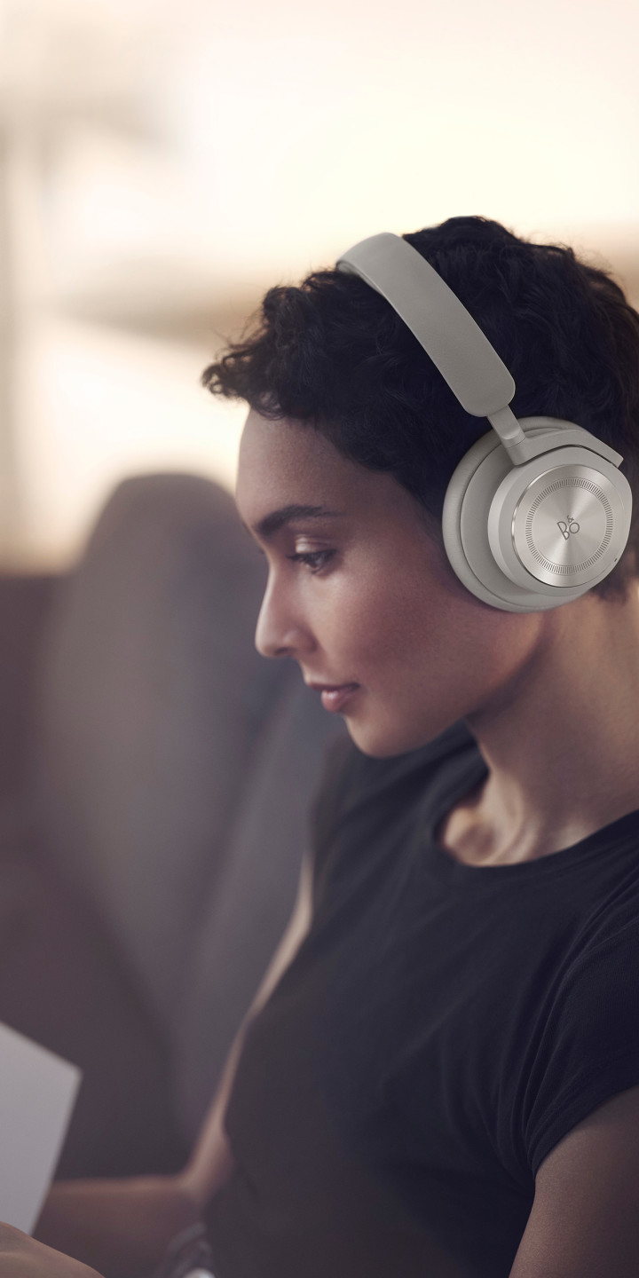 A woman wearing Beoplay HX Sand while working