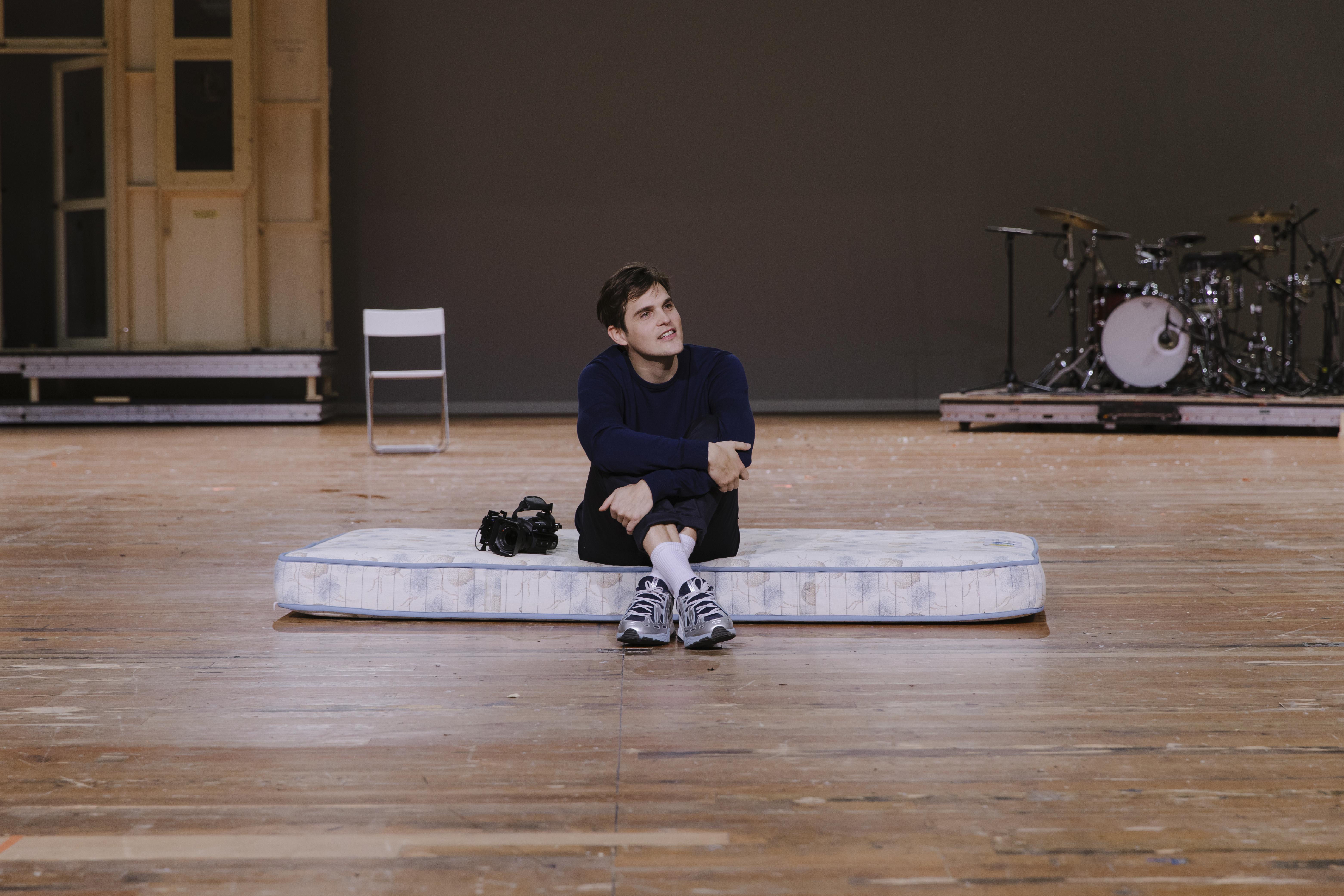 """In a scene from """"Einfach das Ende der Welt"""", actor Benjamin Lillie is sitting on a mattress that lies on the floor."""