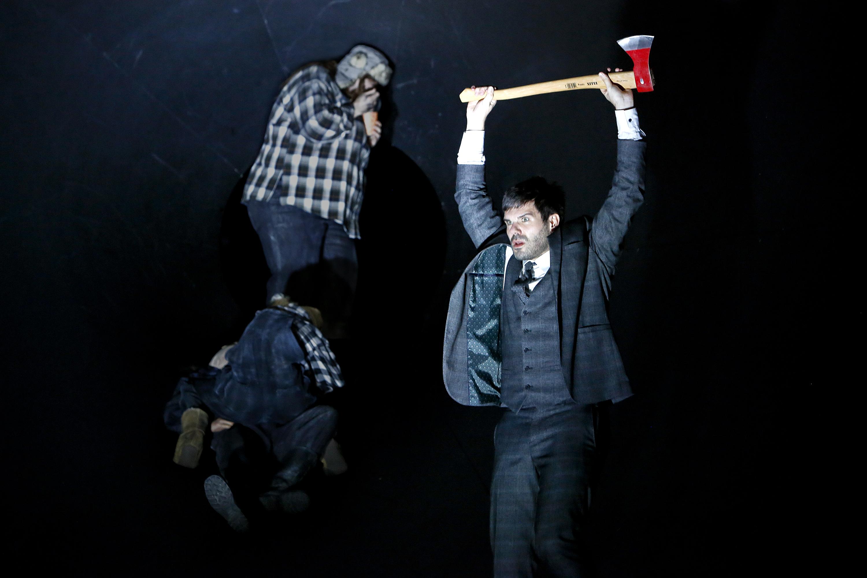 """Szene aus der Inszenierung """"Graf Öderland"""", im Vordergrund hält der Schauspieler Thiemo Strutzenberger eine Axt in die Höhe."""