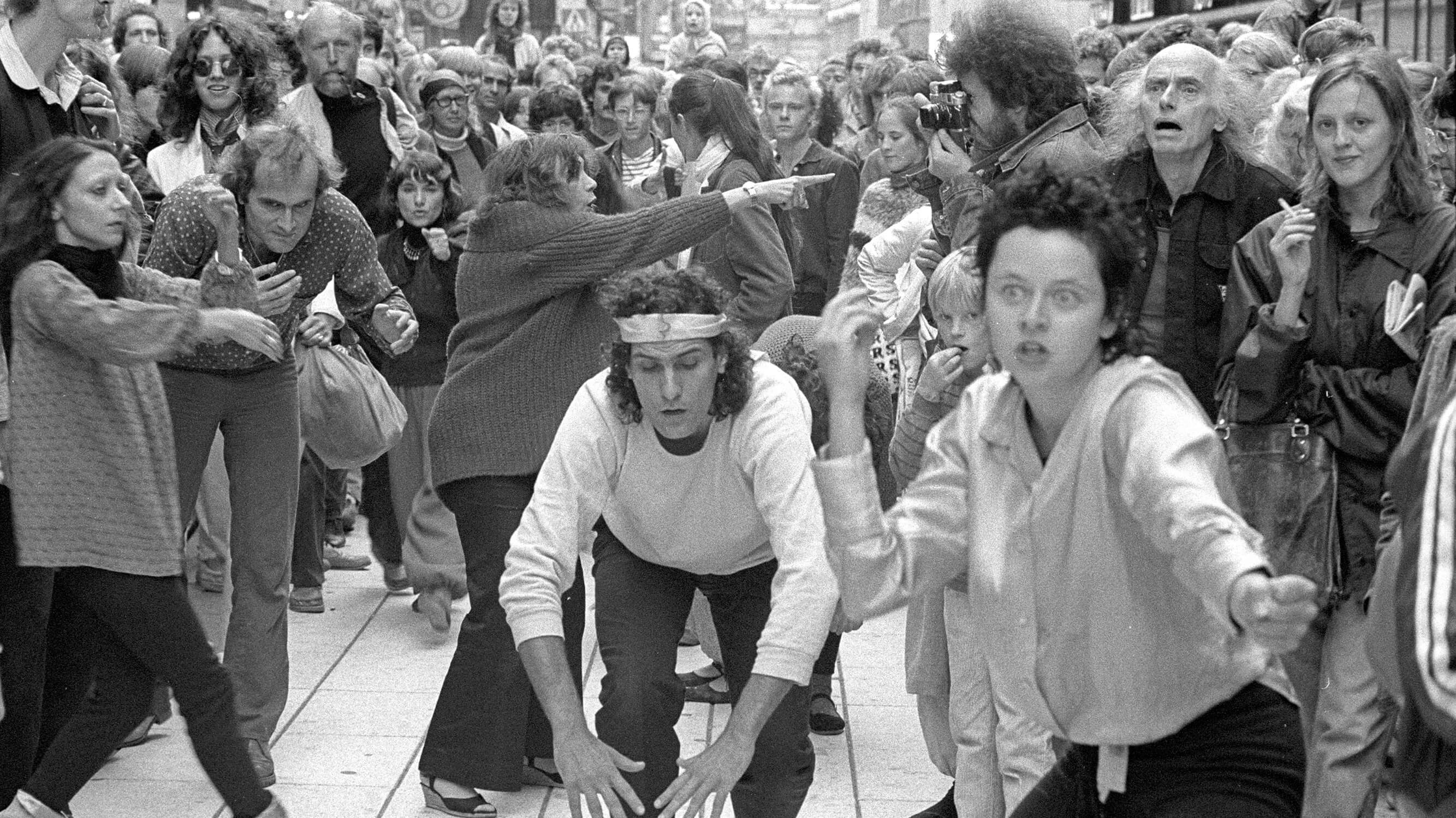 A group of artists is performing street theatre in the middle of a tightly packed mass of spectators.