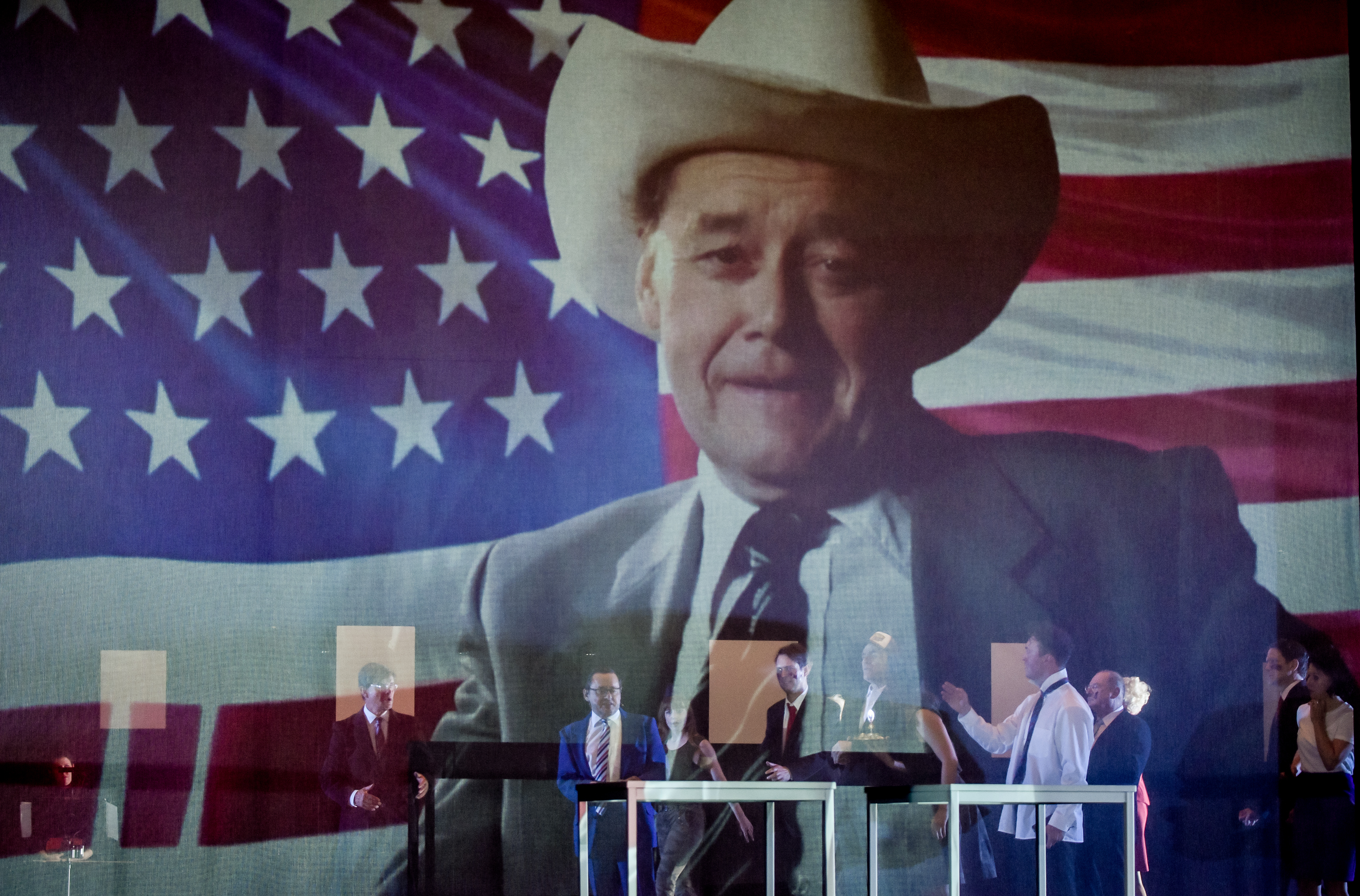 """In a scene from """"Reich des Todes"""", actor Wolfgang Pregler can be seen in a projection, wearing a cowboy hat in front of a US-flag."""
