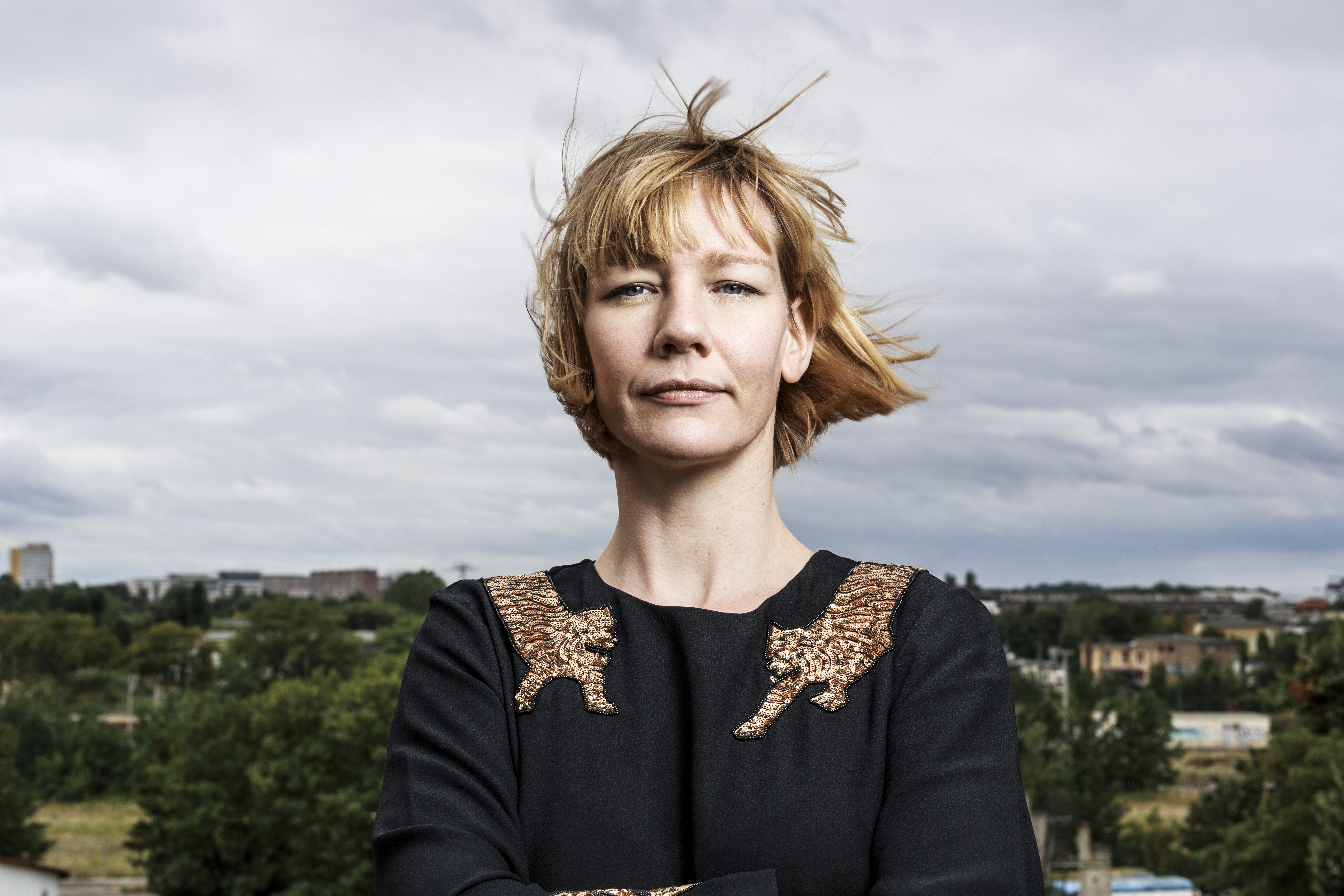 Sandra Hüller is standing in front of a park landscape with scattered houses.