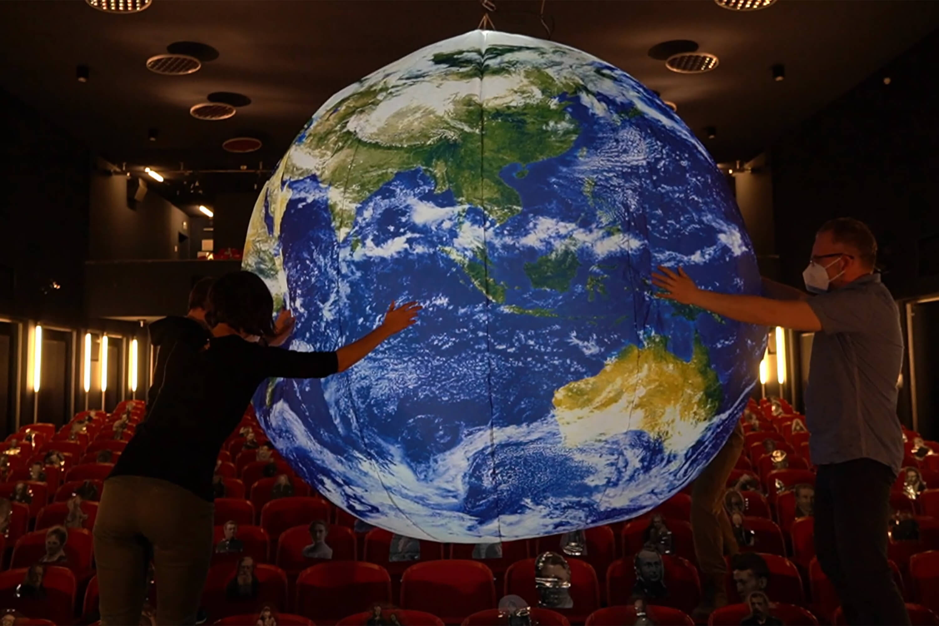 Two people wearing face masks move a globe in front of a theatre's empty auditorium.
