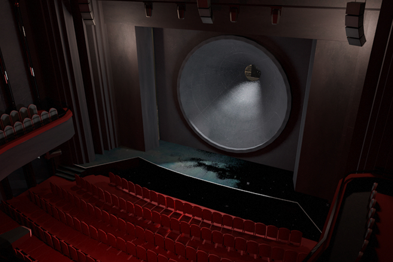 A large, black, walk-in funnel is standing on a stage inside an empty auditorium.