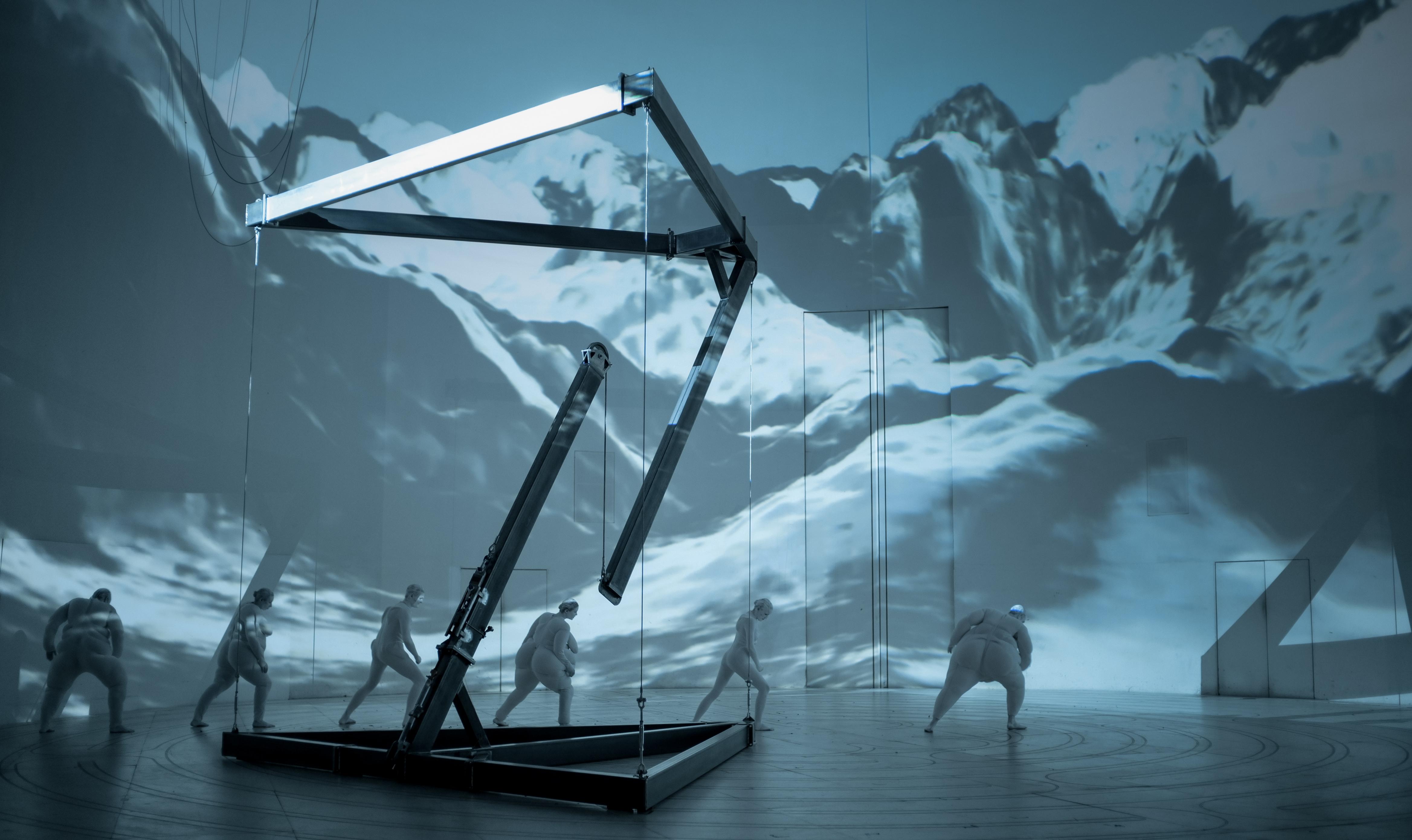 """Szene aus der Inszenierung """"Der Zauberberg"""", mehrere Personen laufen durch einen großen weißen Bühnenraum, im Hintergrund ist eine Schneelandschaft an die Wand projiziert."""