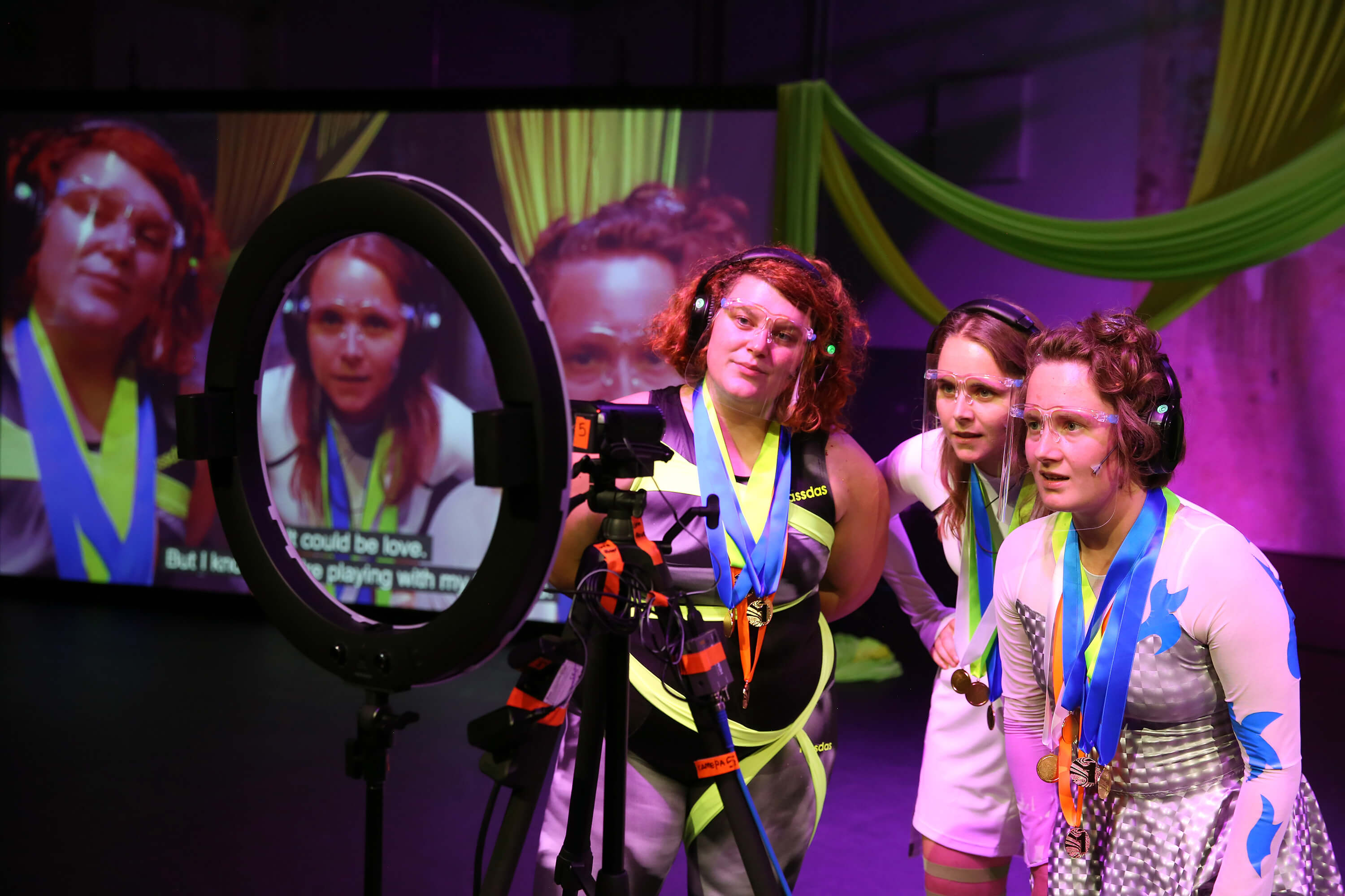 Three women in front of a colourful background are looking into a camera; their image is visible on a screen behind them.