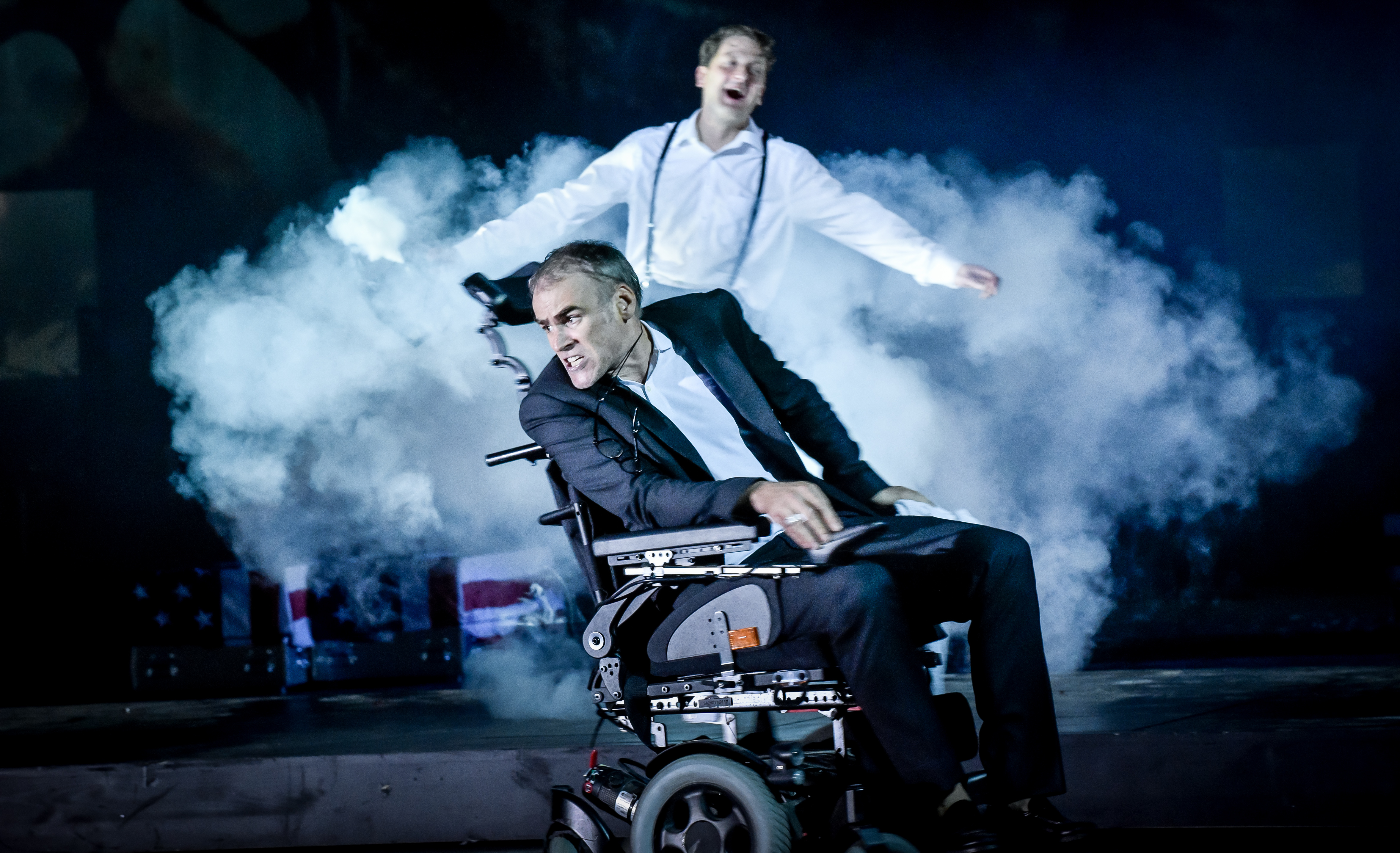 """In a scene from """"Reich des Todes"""", actor Sebastian Blomberg is sitting in an electric wheelchair; with actor Holger Stockhaus standing behind him, swathed in a cloud of fog."""