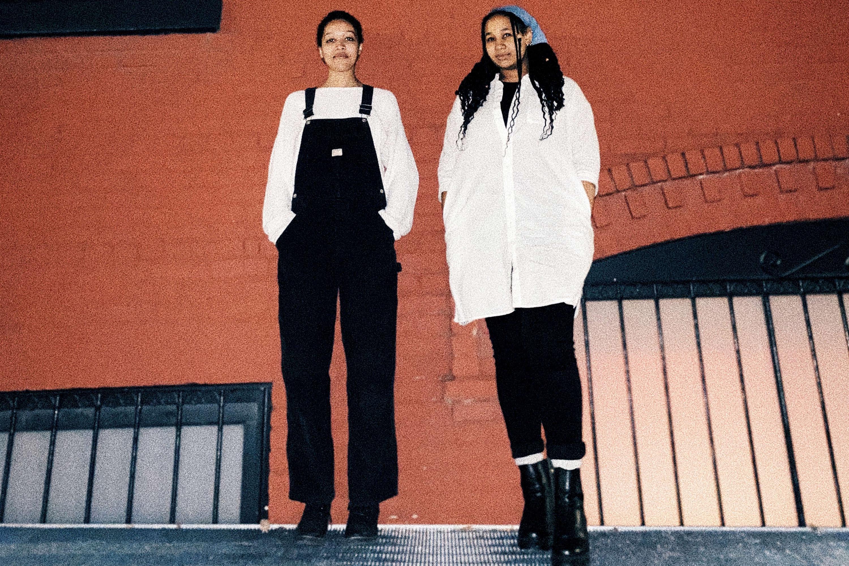Nia Farrell und Talia Paulette Oliveras stehen vor einer roten Ziegelmauer.