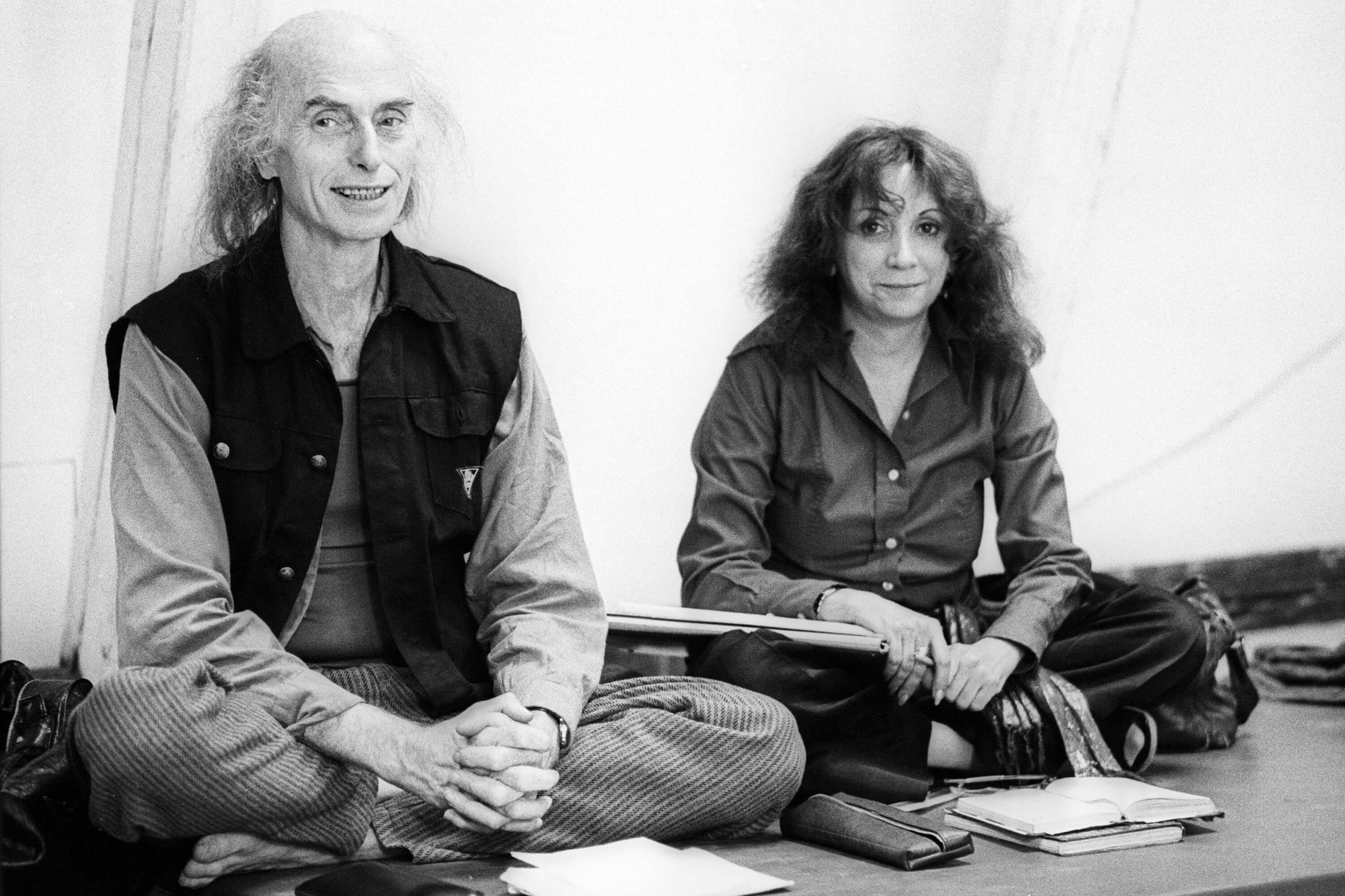 Julian Beck and Judith Malina are sitting next to each other cross-legged.