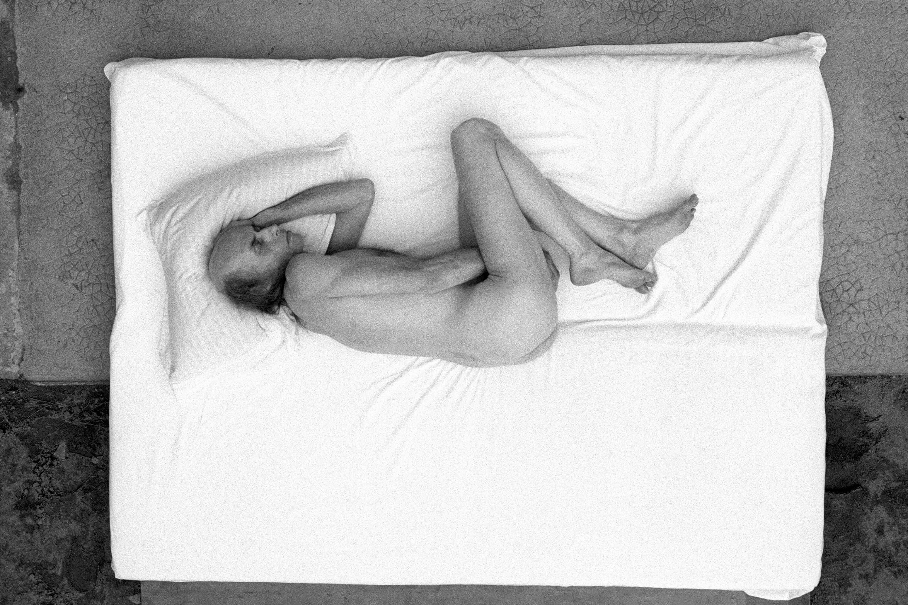 A naked man is lying on his side on a white mattress.