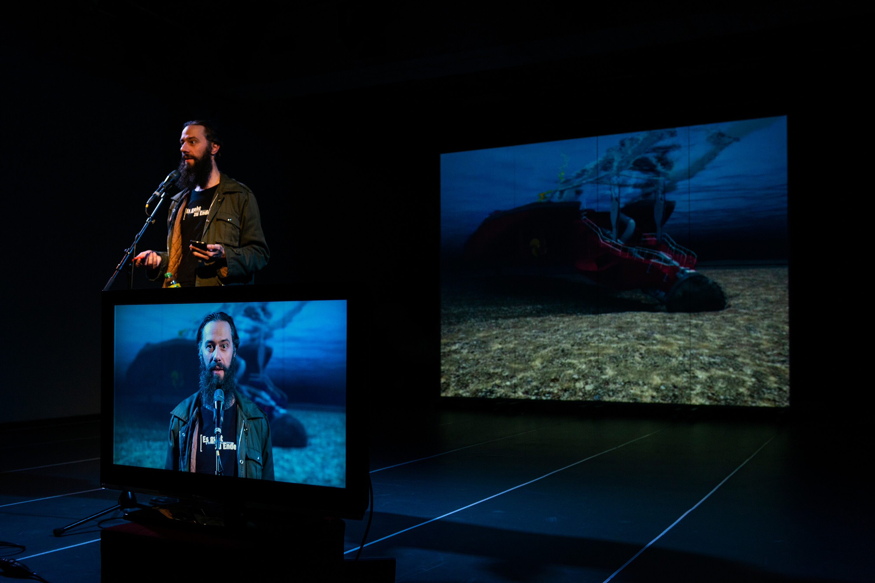 Arne Vogelgesang is standing on a stage with a monitor in front of him and a screen suspended behind him.