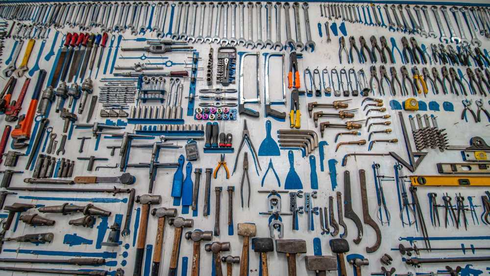 A variety of handheld tools hanging from a wall