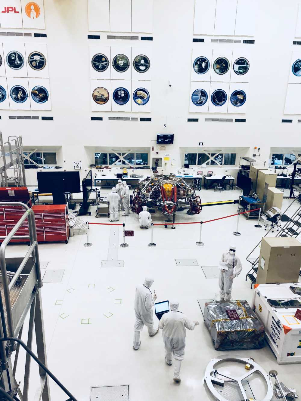 NASA engineers in white clean room suits working on a Mars rover.