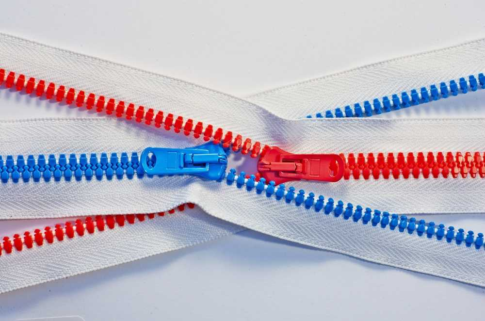 A red zipper and blue zipper interlocked and going in opposite directions.