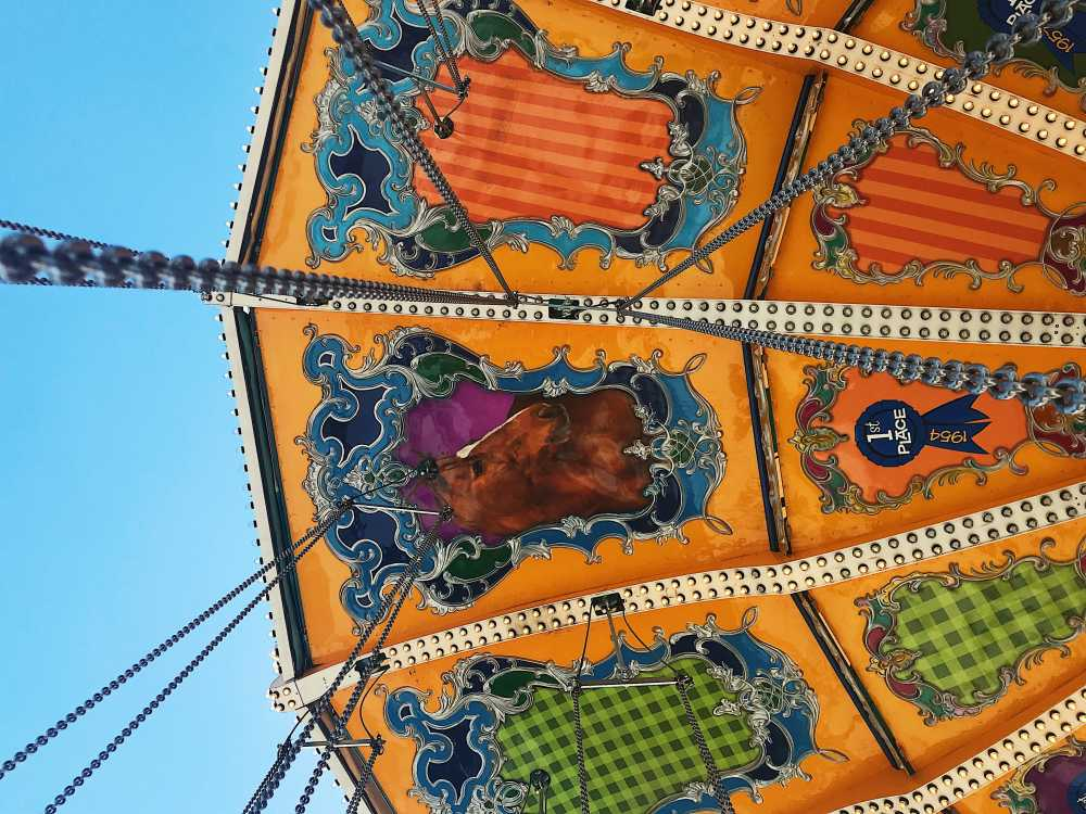 The painted roof of a carousel with the chains that hold the ride together hanging down.