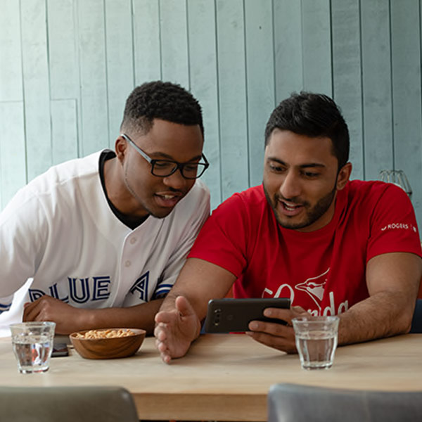 Friends watching a Blue Jays game on their phone while in restaurant