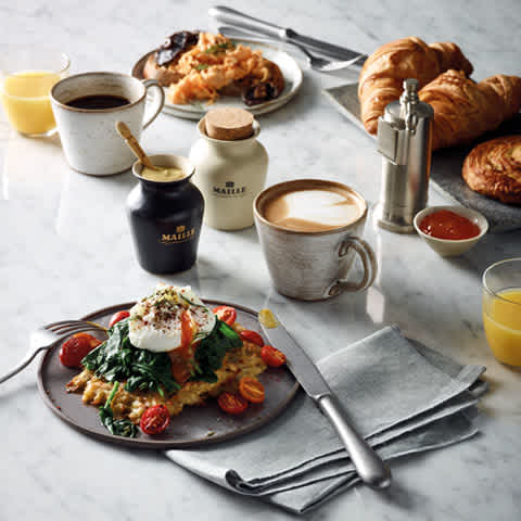 Maille Apéritif and brunch, Breakfast table with eggs, croissant, orange juice, coffee and dressings.