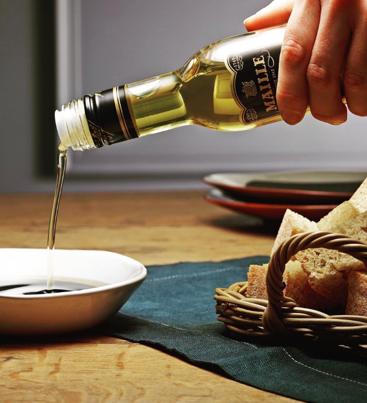 Maille's Olive oil being served onto a white dish