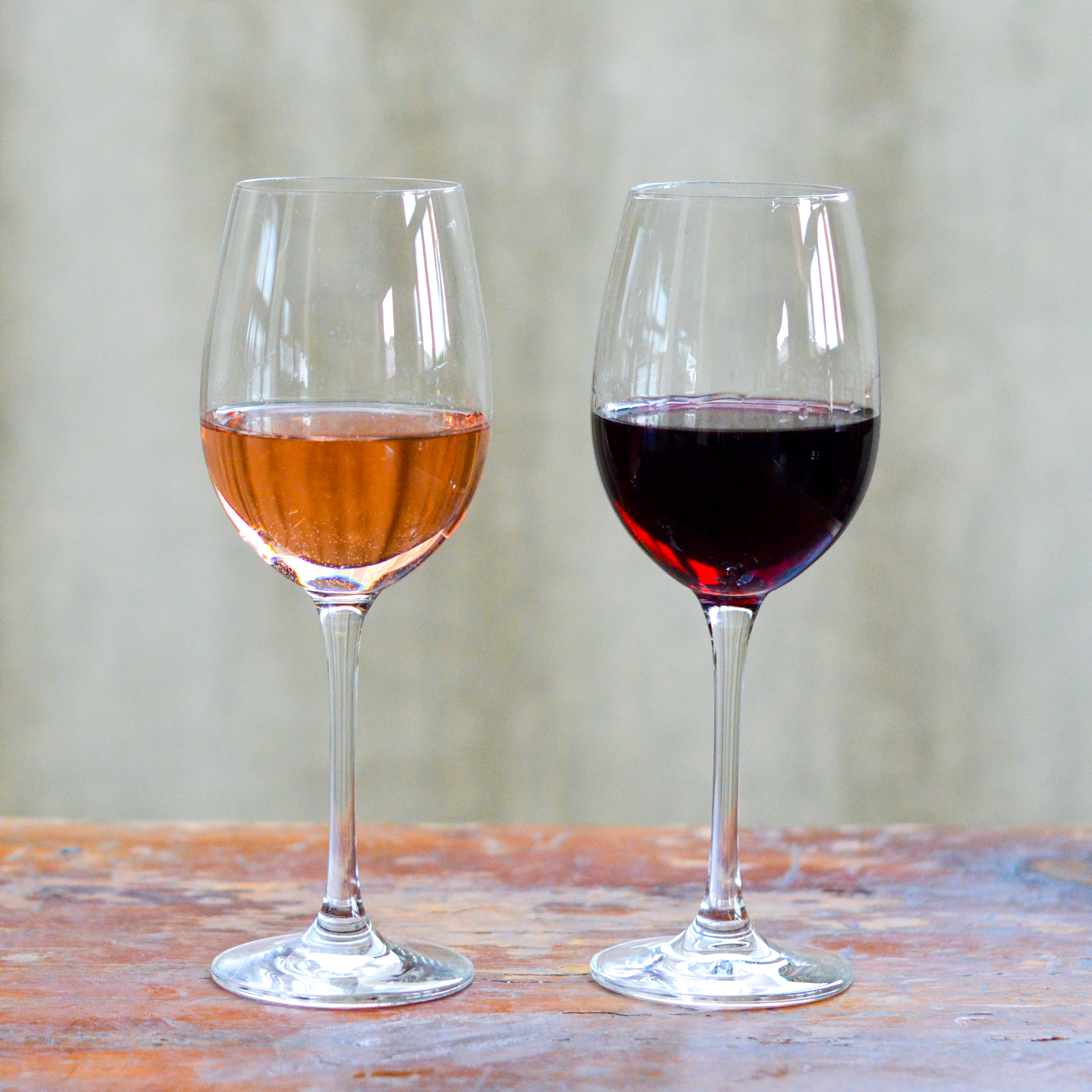 Two glasses of wine on a wooden table