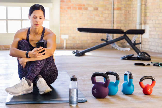 Woman, female, sitting with phone, kettlebells