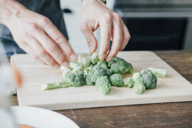 Broccoli on cutting board, with hands
