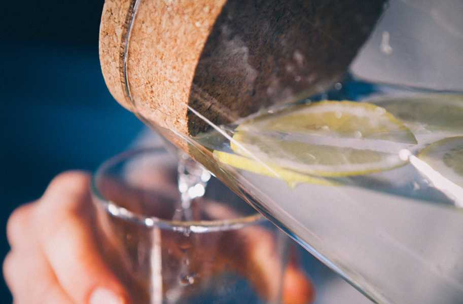 Water pouring into a cup with lemon and cork top