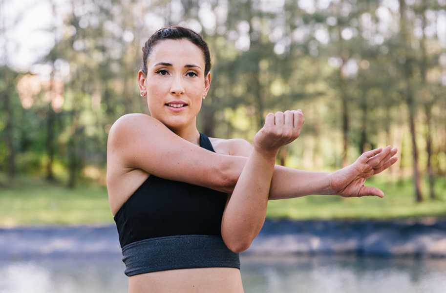 Alba doing shoulder stretch, woman, outside