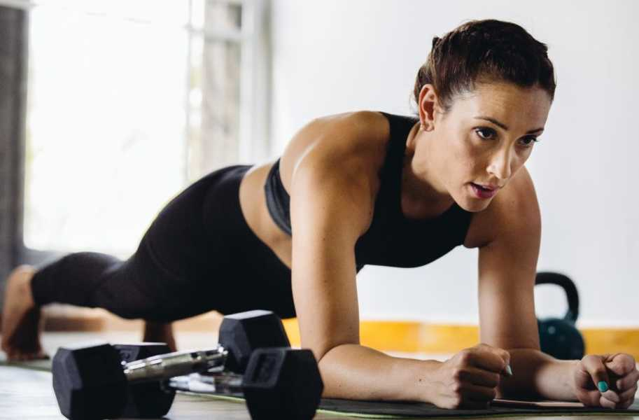 woman planking indoors next to dumbbells