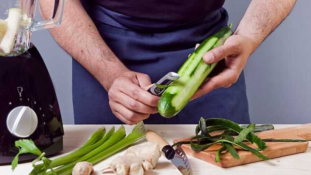Cucumber being peeled, celery and ginger on table