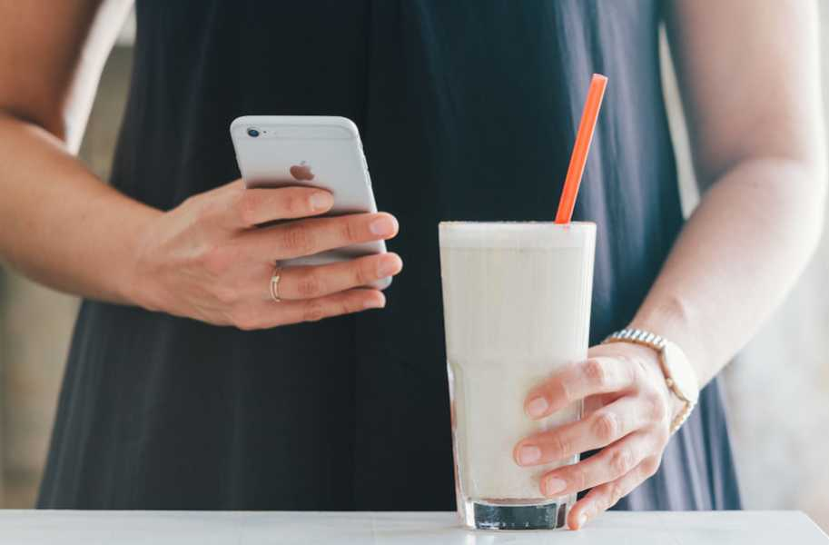 Banana smoothie, milk with straw, iphone in hand
