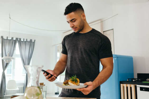 man with smartphone and meal indoors