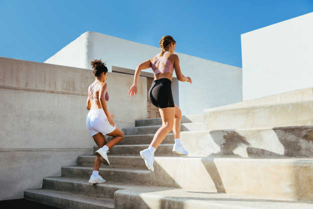 two women running up stairs outdoors