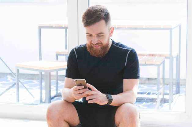 Man with beard, sitting with phone