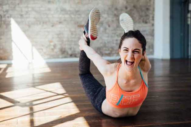 Woman in sports bra stretching with mouth open
