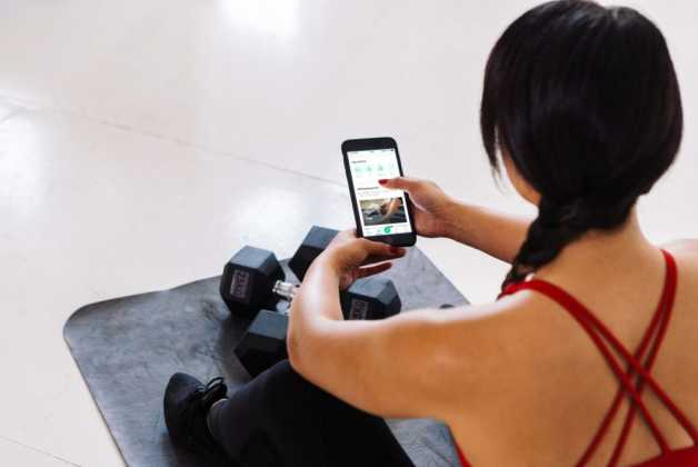 woman on yoga mat with weights and smartphone
