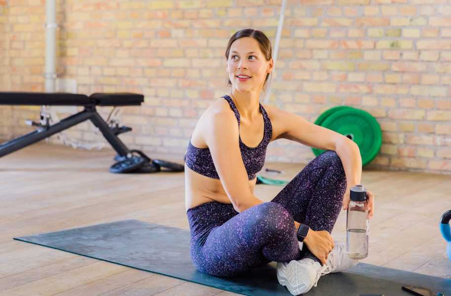 woman sitting on yoga mat indoors