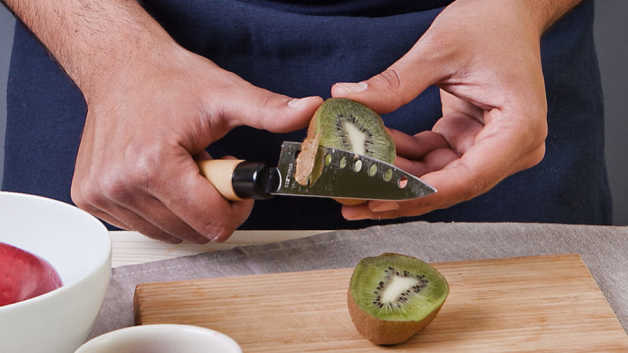 Kiwi being sliced with knife
