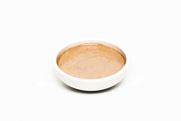 Peanut butter, by itself in a white bowl