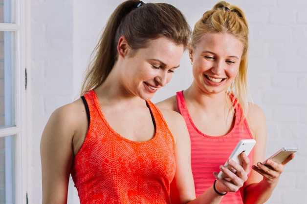 Two women in workout gear looking at phones