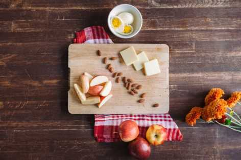 Breakfast  on the go, chopping board with apple, cheese, egg and almonds