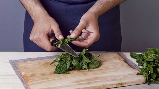 Man's hands chopping mint