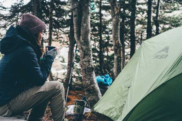 woman camping drinking outside tent