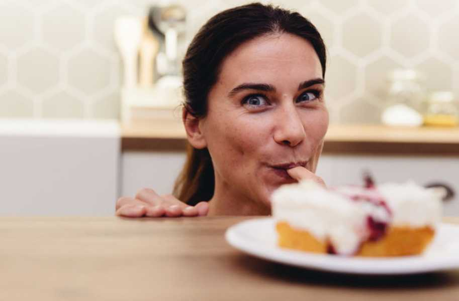 Woman sweets eating kitchen happy