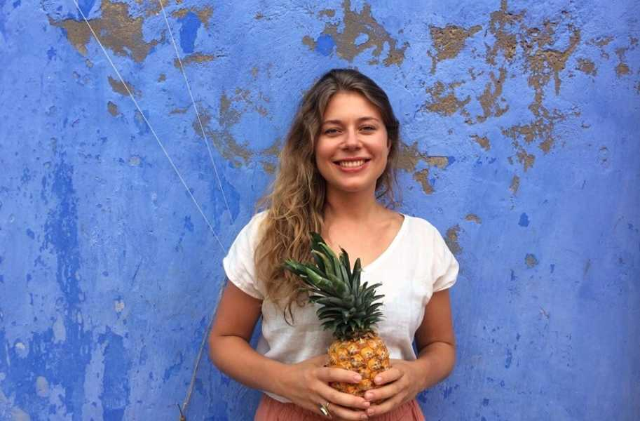 Jenne in front of blue wall with pineapple